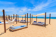 Sun beds on sandy beach in Salema town Royalty Free Stock Images