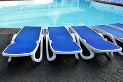 Sun beds by a swimming  pool Stock Photos