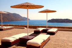 Sun beds on terrace in summer resort(Greece). Royalty Free Stock Image