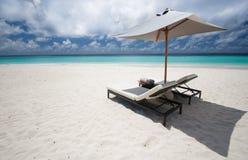 Sun beds and umbrella. Two sun loungers and a beach umbrella near vacant ocean coastline Royalty Free Stock Photos