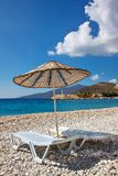 Sun beds and sun umbrella on an empty sea beach on the picturesque pebbles of the Mediterranean Stock Photography