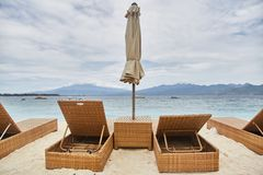 Sun beds with umbrellas on the Bali beach.  royalty free stock photography