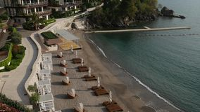 Sun beds and umbrellas on the beach. Montenegrin beaches of the stock footage