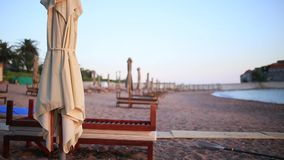 Sun beds and umbrellas on the beach. Montenegrin beaches of the. Adriatic Sea. Sveti Stefan beach stock video footage