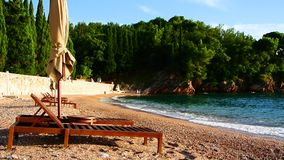 Sun beds and umbrellas on the beach. Montenegrin beaches of the. Adriatic Sea. Sveti Stefan beach stock footage