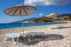 Sun beds and sun umbrellas on an empty sea beach on the picturesque pebbles of the Mediterranean Royalty Free Stock Photo