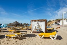 Sun beds, umbrellas and massage pavilion on the Salema beach, Algarve, Southern Portugal Stock Image