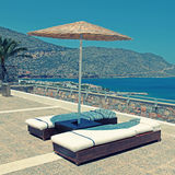 Sun beds and umbrellas on terrace in summer resort Royalty Free Stock Images