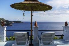 Sun beds under an umbrella in Greece Stock Photos