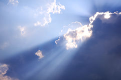 Sun behind. The Sun rays going through dark clouds royalty free stock photography