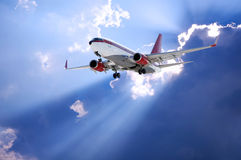 Sun behind and airplane. Airplane and Sun rays going through dark clouds stock photos