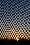 Sun behind cage silhouette on sunrise sky Stock Photo