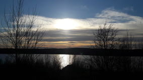 Sun behind clouds above lake. Sunny day with some clouds at natural lake royalty free stock photo