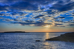 Sun behind clouds above sea level in sunset time Stock Photography