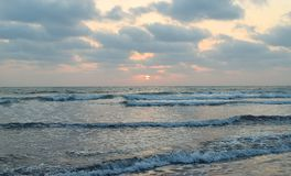 Sun behind Clouds over Infinite Ocean - Natural Sunset Wallpaper Royalty Free Stock Images