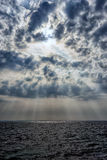 The sun behind the clouds over the sea Stock Photography