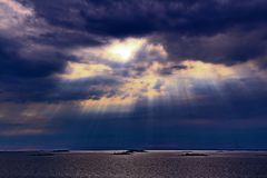 The sun behind the clouds with rays of light shining down on sea royalty free stock photos