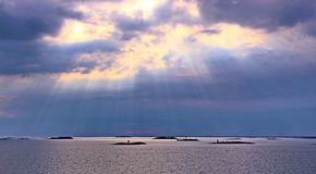 The sun behind the clouds with rays of light shining down on sea stock photography