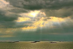 The sun behind the clouds with rays of light shining down on sea royalty free stock image