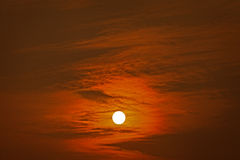Sun behind clouds at sunset Royalty Free Stock Photos