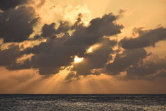 Sun behind the clouds. Sunset from the beach - Saint Martin Royalty Free Stock Photos