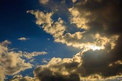 Sun behind dark Cumulus clouds. Stock Image