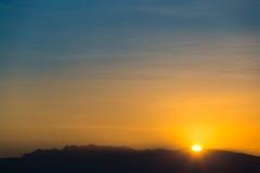 Sun behind dark mountain silhouettes Royalty Free Stock Image