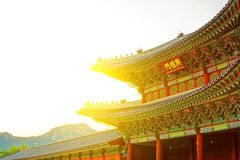 Sun behind roof top of the gate to Gyeongbokgung Palace - translation for this word is Royalty Free Stock Image