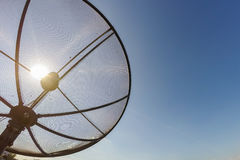 Sun behind satellite receiver with blue sky Royalty Free Stock Photo