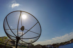 Sun behind satellite receiver with blue sky Stock Image