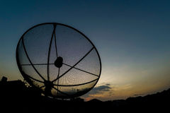 Sun behind satellite receiver in twilight Royalty Free Stock Photos