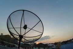 Sun behind satellite receiver in twilight Stock Images