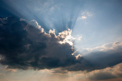 The sun behind storm cloud. The sun and the sun's rays for a dark thundercloud Royalty Free Stock Photography