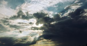 Sun behind storm clouds stock photography