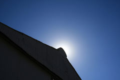 SUN BEHIND TOP OF HANGER. Sun focus above pinacle of hanger roof Stock Image