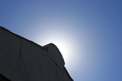 SUN BEHIND TOP OF HANGER. Sun focus above pinacle of hanger roof Royalty Free Stock Image