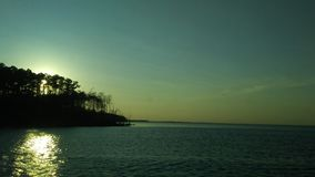 View from boat overlooking treeline with sun behind it reflecting through trees on ocean Stock Photography