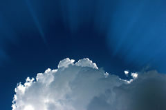 Sun behind the white cloud. Dramatic blue sky with sun rays Stock Photography