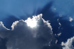 Sun behind the white clouds in the blue sky background Royalty Free Stock Photos