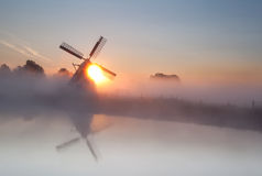 Sun behind windmill and fog Royalty Free Stock Photo