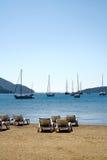 Sun-Bett auf einem Strand und einer Yacht lizenzfreie stockfotografie