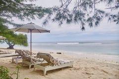 Sun-Betten mit Regenschirmen auf dem Bali-Strand stockbild