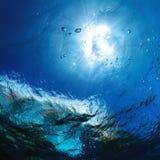 Sun bevattnar den glänsande en ho havet ytbehandlar med luftar bubblar Royaltyfri Fotografi