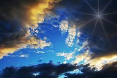Sun beyond clouds. The sun beyond clouds colors their edges in different nuances of yellow and gray Royalty Free Stock Photos