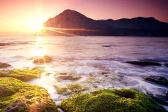Sun Blast with spring moss. The sun blast is shinning along the edge of Mt.The silk-like sea with the foreground of green moss tells that spring is coming stock photo