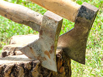 A sun bleached axes stuck in a block of wood.  Royalty Free Stock Photography