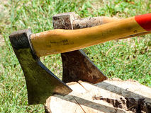 A sun bleached axes stuck in a block of wood Stock Image