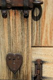 Sun bleached wood door with rusty heart and hardware Royalty Free Stock Photos