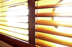 Sun and blinds. Sunlight bursting through wooden slatted blinds Royalty Free Stock Photography