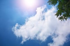 Sun on blue cloudy sky, high resolution picture Stock Photos